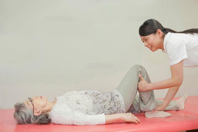 リハビリ施設でシニア女性の介助をする女性介護士 (c)iconics