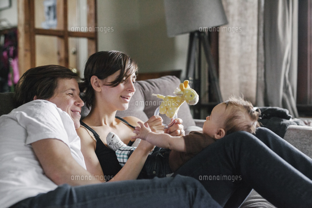 A same sex couple, two women looking at their 6 month old baby girl.