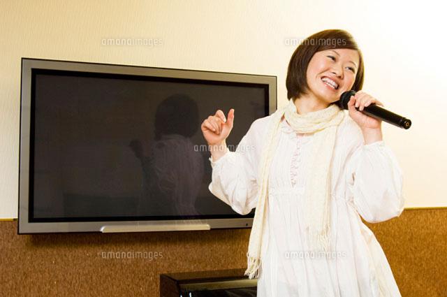 カラオケで歌う女性 (c)DAJ