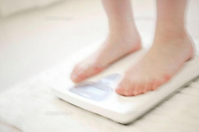 体重計に乗る女性の足元 (c)daj