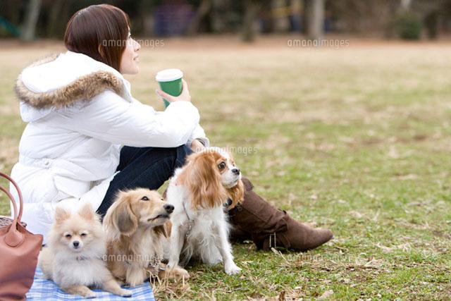 芝生でリラックスする犬と女性 (c)DAJ