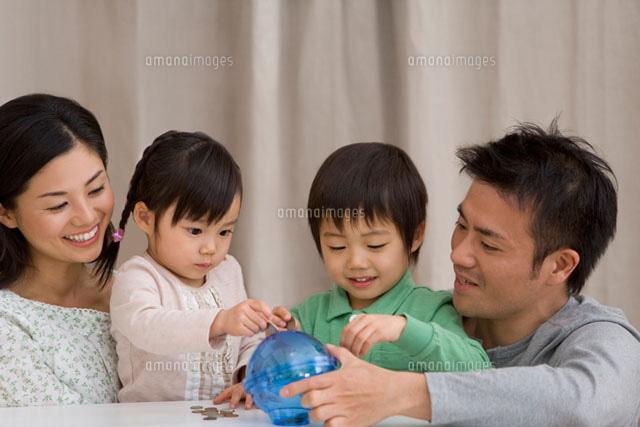 地球の貯金箱にお金を入れる家族 (c)DAJ