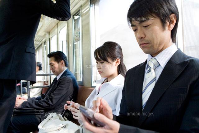 電車内でPDAを見るビジネスマン (c)DAJ