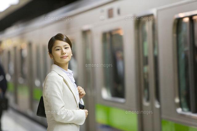 駅のホームに到着した電車を見るOL (c)DAJ