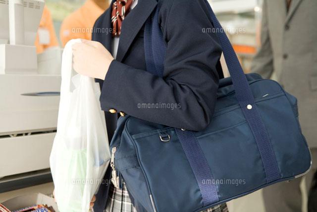 コンビニで買い物をする女子高生 (c)DAJ