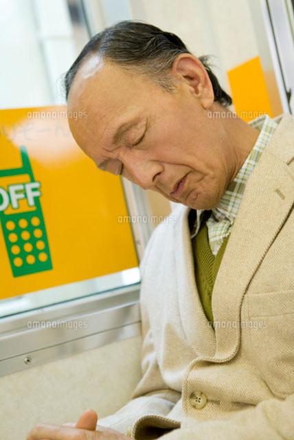 電車の座席に座り居眠りをするシニア男性 (c)DAJ