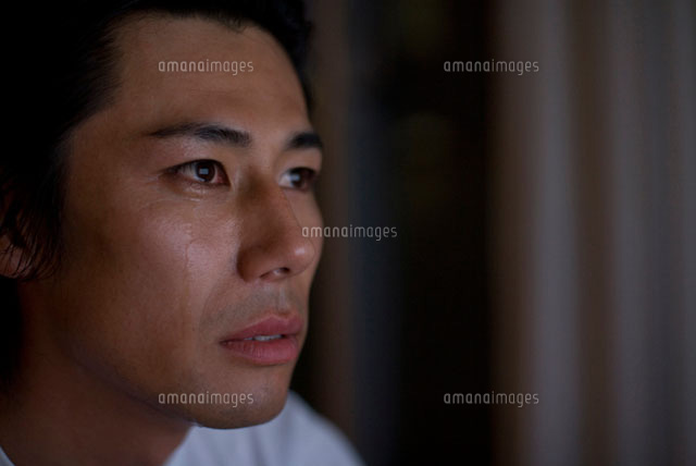暗い部屋で涙を流す男性 (c)DAJ