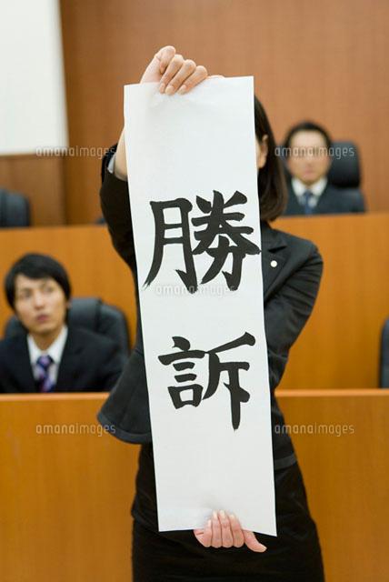 勝訴の紙を持った若い女性 (c)DAJ