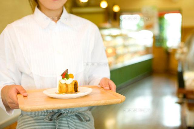 トレイに載せたケーキを運ぶ女性 (c)ELEMeNT