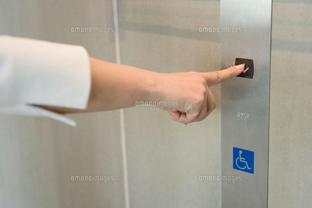 エレベーターのボタンを押す手 (c)DAJ