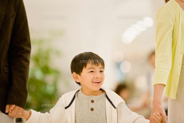 両親と手を繋ぐ男の子 (c)DAJ