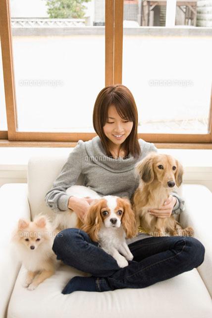 ソファでくつろぐ女性と犬 (c)DAJ