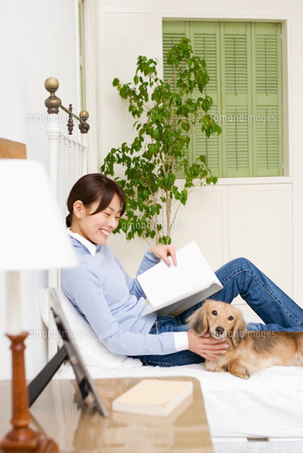 ベッドでくつろぐ女性と犬 (c)DAJ