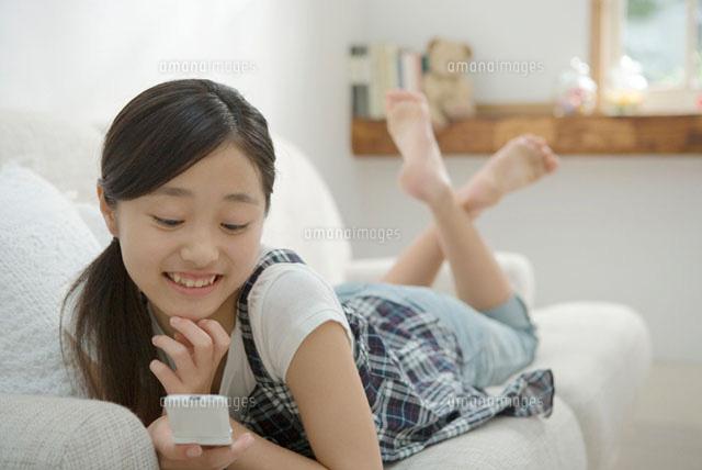 ソファで携帯電話を見る女の子 (c)DAJ