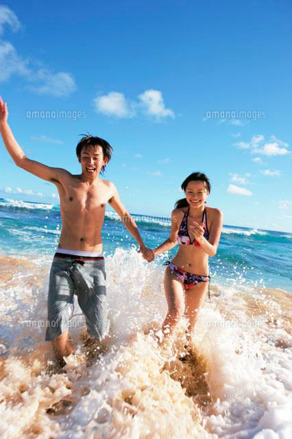 海で遊ぶカップル (c)daj