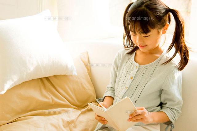 ソファで本を読む日本人の女の子 (c)LUSH LIFE/a.collectionRF