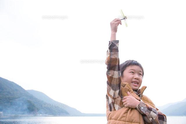 湖畔で作ったトンボのおもちゃで遊ぶ男の子 (c)Tomozo/a.collectionRF