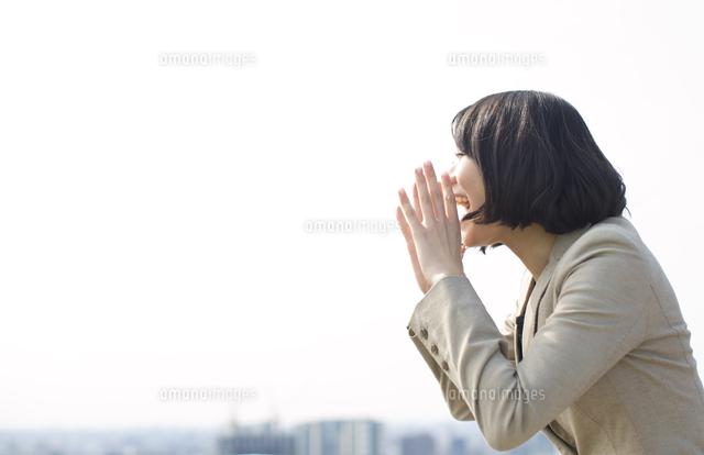 手を口にあてて大声を出すビジネス女性 (c)apjt