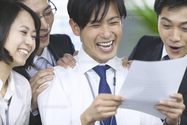 紙資料を見て喜ぶビジネス男女 (c)apjt