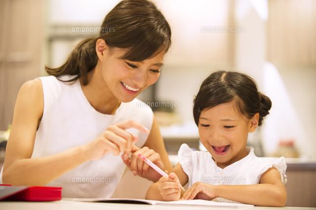 子供の勉強を見る母親 (c)apjt