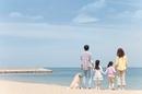 海を眺めている家族と犬の後姿