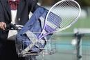自転車のかごに入ったテニスラケットとカバン