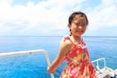 沖縄の海上のボートで笑顔を見せる少女