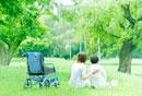 芝生に座るシニア女性と看護師の後ろ姿