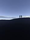 シルエットの丘と握手する2人