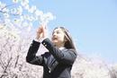桜の下で写真を撮る女子中学生