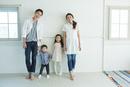 白い壁の前に並ぶ家族