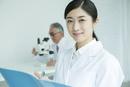 白衣を着た30代女性と顕微鏡を覗く男性