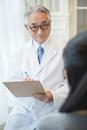 白衣を着た70代男性医師と患者