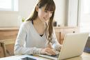 笑顔でパソコンを操作する20代女性