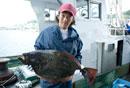 獲れた魚を手に持つ漁師