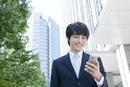 携帯電話を見る笑顔のヤングビジネスマン
