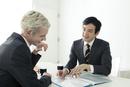 会議中のスーツ姿の20代の外国人男性と日本人男性