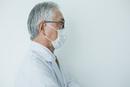 白衣を着てマスクをした70代男性横顔