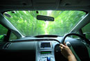 新緑の道を走るハイブリッドカーの運転席