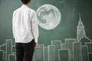 ビル群と満月が描かれた黒板イラストの前に立つ人