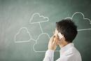 黒板に書かれた複数の繋がった雲の前で電話をする人