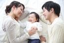 赤ちゃんを中心にベッドで笑う若い3人家族