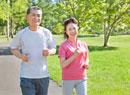 緑の中でジョギングするトレーニングウェアの60代シニア夫婦