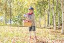 紅葉の中、リンゴを持つ6歳の男の子