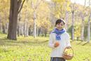 紅葉の中、カボチャを持つ6歳の女の子