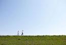 青空の堤防をジョギングしているシニア夫婦