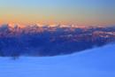 千畳敷カールの雪原の地吹雪と南アルプスと富士山の夕景