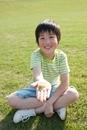 公園の芝生に座って手にカエルを乗せる男の子