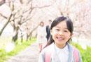 桜の木の下に立つ笑顔の女の子とそれを見守る両親
