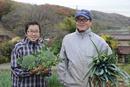 収穫したネギとブロッコリーを持つ農婦